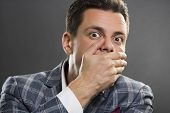 stock photo of taboo  - Portrait of afraid businessman wearing suit covering his mouth with his hand over grey background - JPG