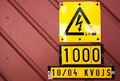 Yellow High Voltage Caution Sign On Red Wooden Wall