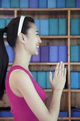 Side view of young women doing yoga with hands clasped together