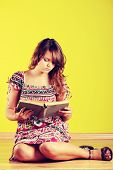 Teen woman sitting on the flor and reading a book