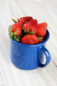 A blue speckled cup on a rustic farmhouse style kitchen table filled with freshly picked ripe strawb