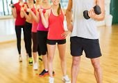 fitness, sport, training, gym and lifestyle concept - group of people working out with dumbbells in