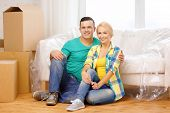 moving, home and couple concept - smiling couple sitting on the floor in new house