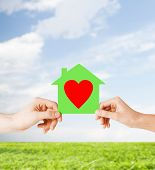 charity, real estate and family home concept - isolated picture of male and female hands holding gre