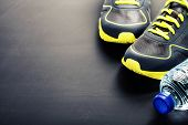 image of relay  - Sport shoes and water on grey background - JPG