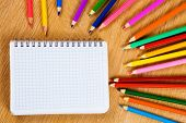pic of pencil eraser  - Colored pencils and notepad on wooden table - JPG