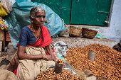 TIRUCHIRAPALLI, INDIA - FEBRUARY 14, 2013: Unidentified Indian woman - hawker (street vendor) of fried peanuts