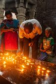 TIRUCHIRAPALLI, INDIA - FEBRUARY 14, 2013: Unidentified Indian family father mother son worshipping by lighting ghee lamps in Hindu tempe Sri Ranganathaswamy Temple
