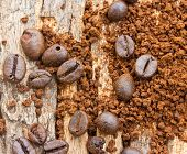 Coffee Beans And Coffee Grind Beans On Wood Background .