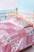 Photo of girl's bed with pattern bedding on it