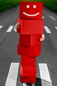 Smiling manikin made of red boxes standing on the street