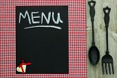 Chalkboard menu sign with cast iron spoon and fork on red checkered tablecloth