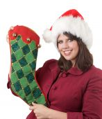 Young woman in Santa hat holds a Christmas stocking; isolated