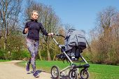 stock photo of buggy  - Young mother jogging with a baby buggy - JPG
