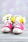 Beautiful gumshoes with flowers inside on wooden table, on light background