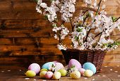 Composition with blooming branches and Easter eggs in  wicker basket on wooden background