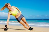 Young attractive woman doing kettle bell exercises outside. Fitness woman working out at the beach. Crossfit exercise.