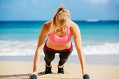 Young attractive woman doing push ups outside with barbells. Fitness woman working out at the beach.