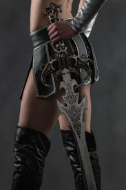 stock photo of independent woman  - Performer woman wearing sexy costume and holding a sword grey smoky background - JPG