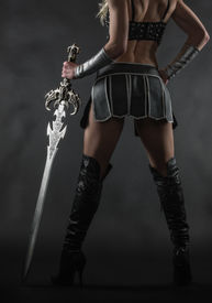 image of sword  - Performer woman wearing sexy costume and holding a sword grey smoky background - JPG