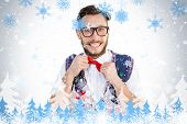 Geeky hipster wearing christmas vest against snowflakes and fir trees