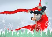 Break dancer doing a handstand against snowflakes and fir trees in green