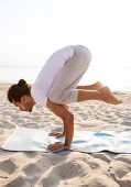 fitness, sport, people and lifestyle concept - man doing yoga exercises on mat outdoors