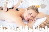 Pretty young woman receiving a massage with hot stone against fir tree forest and snowflakes