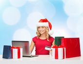 christmas, holidays, technology and shopping concept - smiling woman in santa helper hat with gifts, credit card and laptop computer over blue lights background