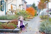 Little Toddler Girl With Curly Hair Sitting On The Front Yard Of House In Beautiful Street In Autumn
