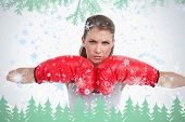 Serious woman with boxing gloves against frost and fir trees in green
