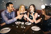 Composite image of Laughing friends sitting together clinking glasses against snow