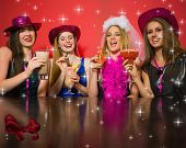 picture of hen party  - Laughing friends having hen party holding cocktails against digitally generated red shiny bow - JPG