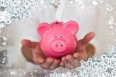 Composite image of casual businessman holding piggy bank against snow