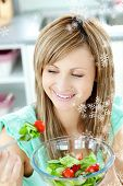 Young woman eating a salad in the kitchen with snow falling