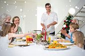 Composite image of Family enjoying Christmas meal at dining table against snow