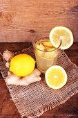 Ginger drink and ginger root and lemon on sackcloth napkin on wooden table on wooden background