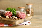 Italian salami on wooden cutting board, on wooden background