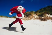 Santa Claus walking along the beach in an out of context situation