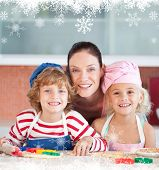 Radiant mother baking with her children against fir tree forest and snowflakes