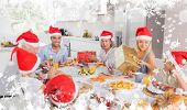 Composite image of a Smiling family around the dinner table at christmas against snow