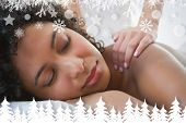 Gorgeous woman enjoying a shoulder massage against fir tree forest and snowflakes