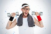 Geeky hipster lifting dumbbells in sportswear against snow falling
