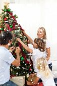 Composite image of Joyful family decorating Christmas tree with snow falling
