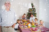 Composite image of Smiling grandfather standing at the dinner table against snow falling