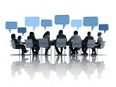 Business People Discussing Around The Conference Table And Speech Bubbles Above Them.