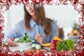 Composite image of pretty woman eating a vegetarian salad against snow