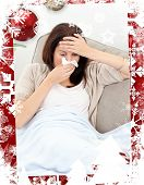 Tired woman feeling her temperature while blowing her nose against christmas themed frame