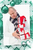 Mature man in winter clothes holding gifts against christmas frame