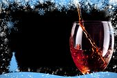 Composite image of snow frame against empty stemware being filled with wine